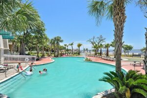 Pristine beachfront condo, kids playing in the large resort style pool